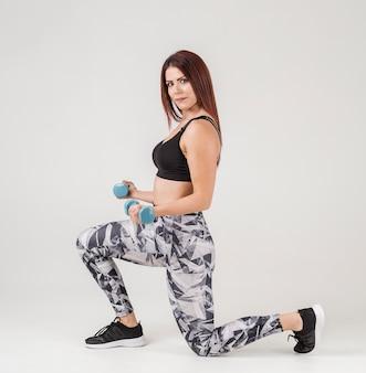 Vista laterale della donna che si esercita con i pesi