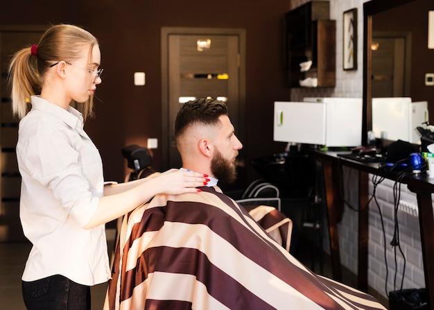 Женщина сбоку готовится к стрижке для своего клиента