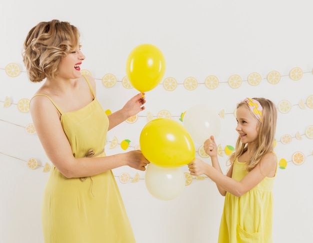 Side view of woman and girl posing with balloons and smiling