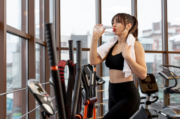 Side view woman at gym hydrating
