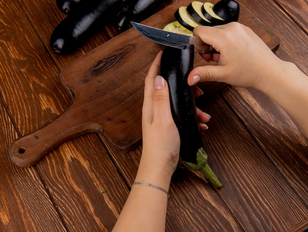 Side view of woman hands cutting eggplant with knife on cutting board with whole ones on wooden background