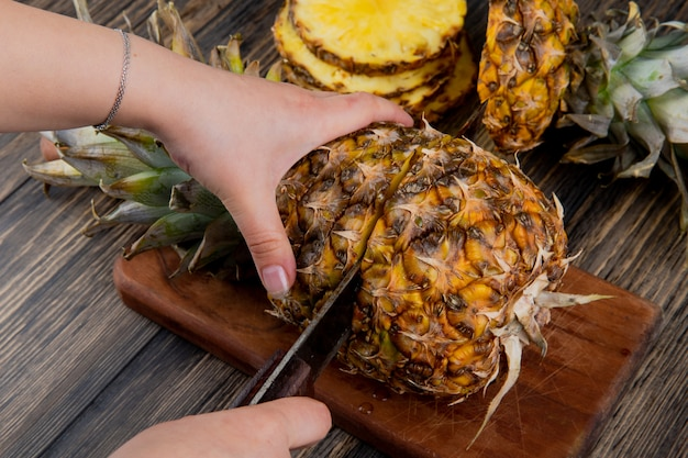 Side view of woman hands cutting pineapple with knife on cutting board with sliced pineapple on wooden background