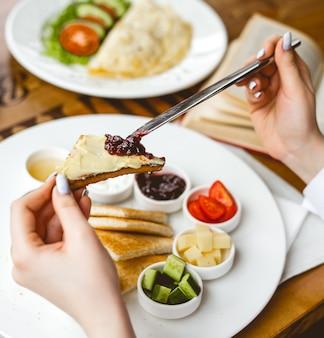 Vista laterale una donna fa colazione toast fritto con marmellata di panna acida al burro miele e olive su un piatto