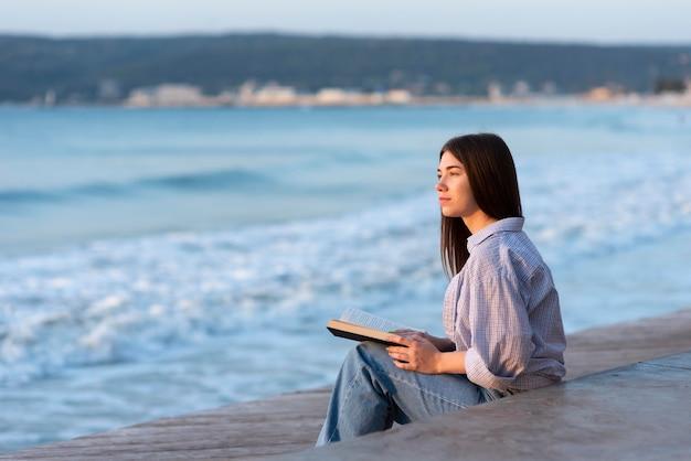 Вид сбоку женщина, держащая книгу с копией пространства