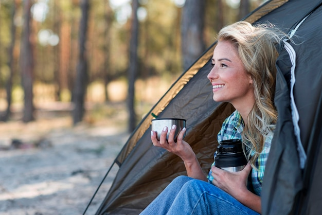 一杯のコーヒーを保持している側面図の女性