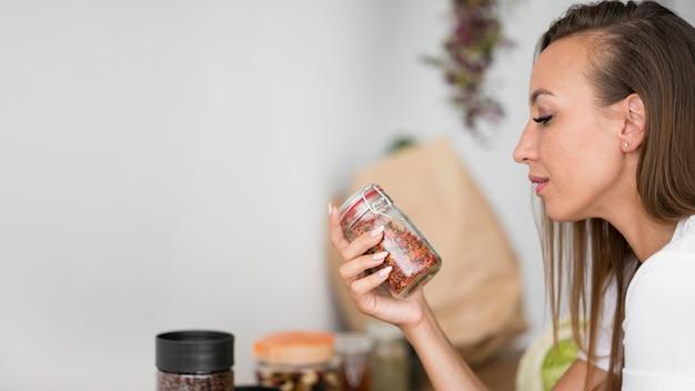 スパイスと瓶を保持している側面図の女性