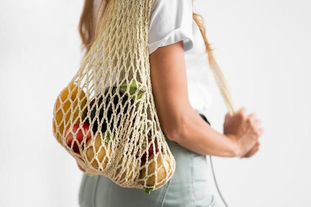 Вид сбоку женщина, держащая перерабатываемый мешок