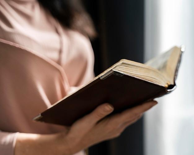 Vista laterale della donna che tiene la bibbia