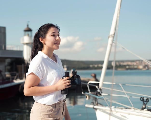Side view woman holding binoculars