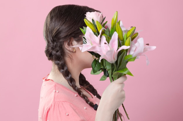 Side view of woman holding bouquet of lilies over face
