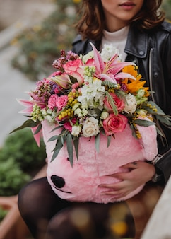 Side view of a woman holding a bouquet of pink and white color roses with pink color lilies mimosa eustomas pink color spray roses and greenery