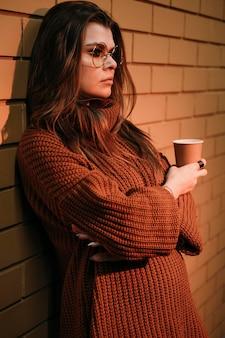 コーヒーカップを保持している側面図の女性