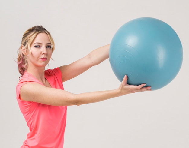 Side view of woman holding exercise ball