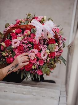 Side view of a woman holding a flower composition with pink roses eustoma and eucalyptus in a wicker basket