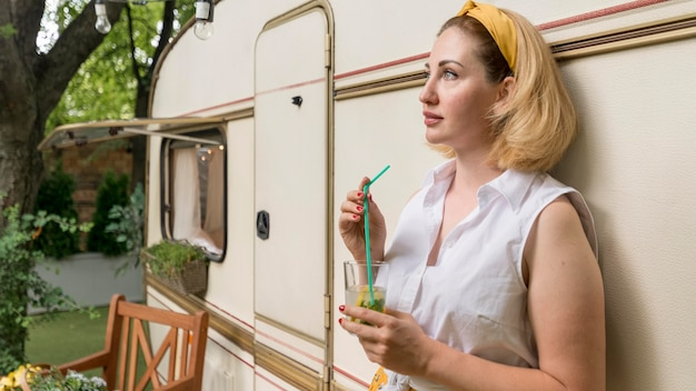 Side view woman holding a glass of lemonade next to a caravan