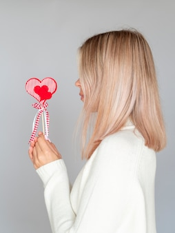 Side view of woman holding heart