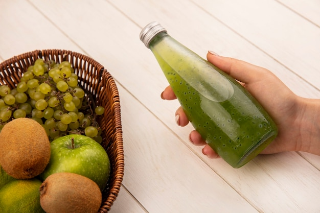白い壁の上のバスケットにリンゴキウイとブドウのジュースボトルを保持している側面図の女性