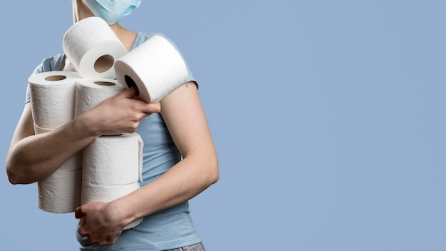 Side view of woman holding many toilet paper rolls while wearing medical mask