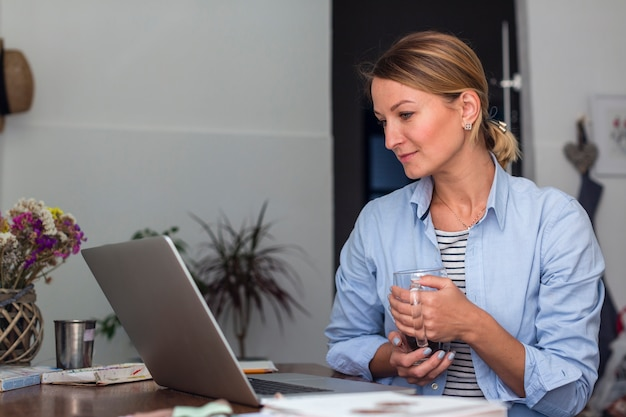 Side view of woman holding mug and looking at laptop