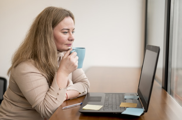 Side view of woman holding mug and working on laptop at the office