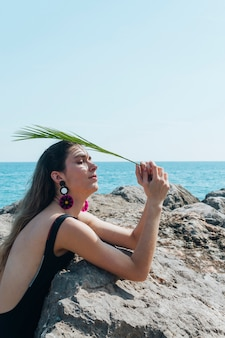 Side view of woman holding palm leaves over her head