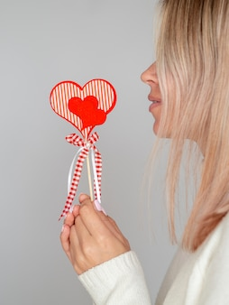 Side view woman holding paper heart