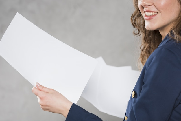 Side view of woman holding papers