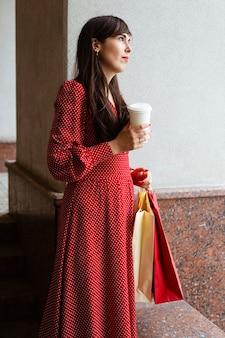 Vista laterale della donna che tiene i sacchetti della spesa e caffè