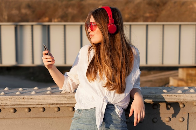 Side view of woman holding smartphone while wearing sunglasses and headphones