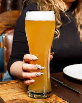 Side view of a woman holding a tall glass of light beer
