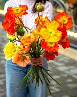 Side view of a woman holding yellow and red anemone flowers bouquet jpg