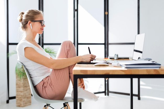 Side view of woman at home desk working