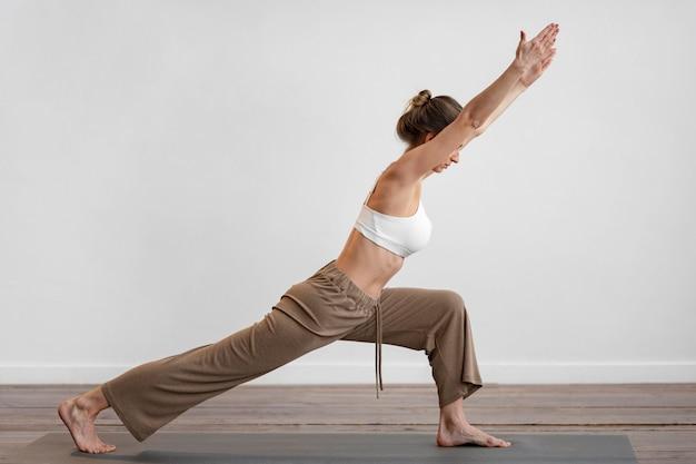 Vista laterale della donna a casa a praticare yoga con copia spazio