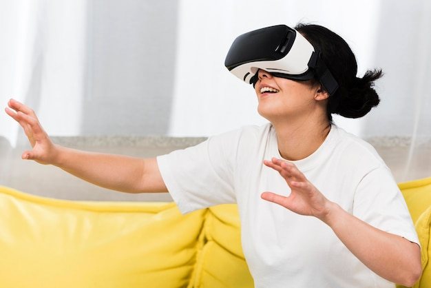 Side view of woman at home using virtual reality headset