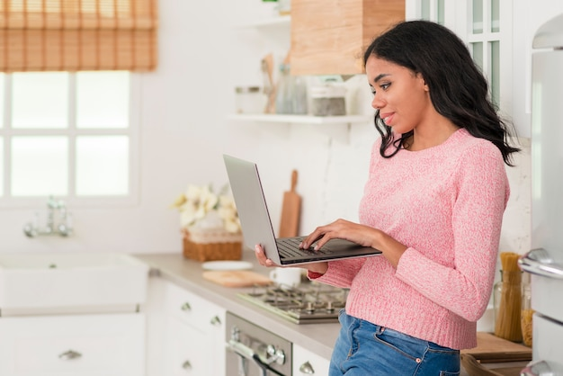 Side view woman at home with laptop