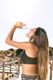 Side view woman hydrating after running