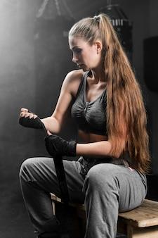 Вид сбоку женщина в спортивной одежде, сидя на скамейке в тренажерном зале