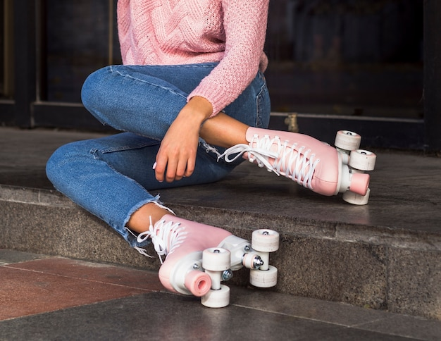 Side view of woman in jeans on stairs with roller skates
