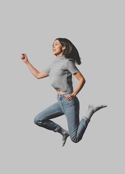 Vista laterale della donna che salta in aria