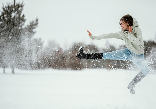 Side view of woman jumping outdoors in winter