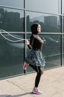Side view of woman jumping rope