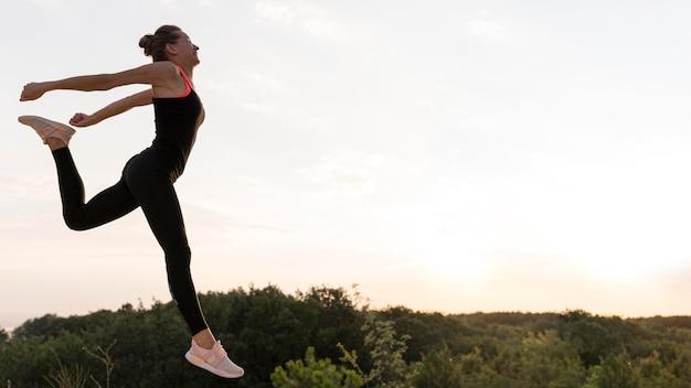 Вид сбоку женщина прыгает с копией пространства