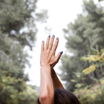 Side view of woman lifting hands in yoga pose outdoors