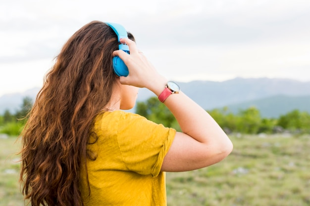 Side view of woman listening to music on headphones in nature