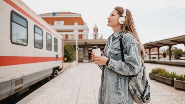 기차 플랫폼에서 음악을 듣고 측면보기 여자