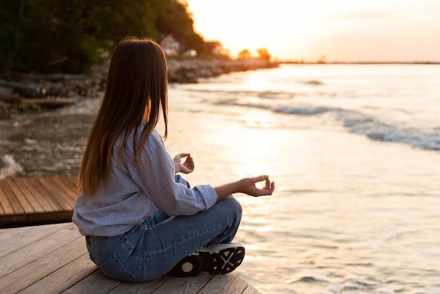 Вид сбоку женщина смотрит на море на закате с копией пространства