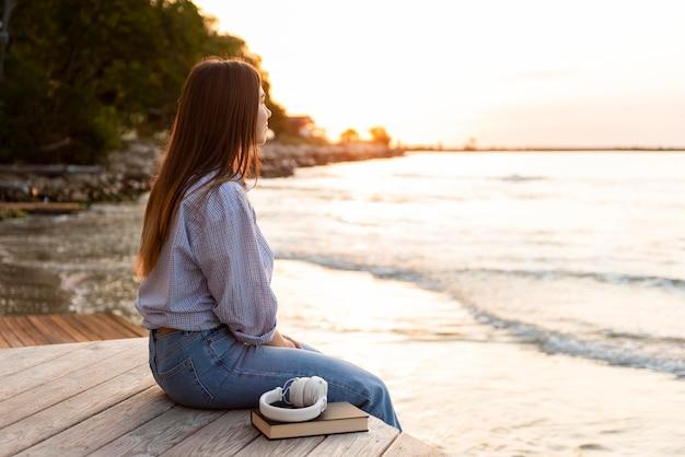 Вид сбоку женщина смотрит на море на закате