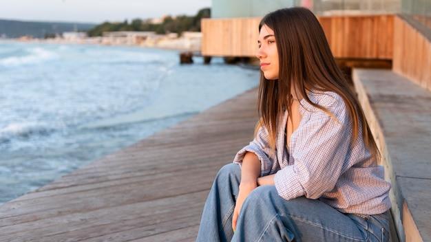 Вид сбоку женщина смотрит на море