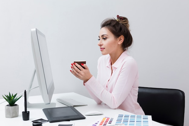 Side view of woman looking at computer while holding cup of coffee