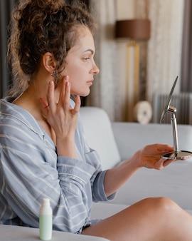 Donna di vista laterale che osserva in specchio Foto Gratuite